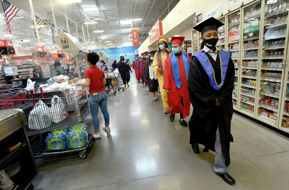 """Young employees graduating from area high schools and colleges wear their caps and gowns as they process past the check-out lanes to be honored with a special commencement celebration at the H-E-B on College Street Wednesday. Nineteen of the stores employees are graduating this season. The group wore their respective caps and gowns, sitting in an area near the store front, with a stage and decorations set to celebrate their achievement. Derwin Samuels, Director of Human Resources for BISD, who worked at H-E-B throughout high school and college, was the event keynote speaker, and relayed how the experience they have garnered in their time as employees will carry forward as they move into their futures. Store Director Natosha Coleman concluded the ceremony, telling the group of graduates and the friends and families in attendance, """"I feel like I'm a kind of a mom to all of you when you're here working, so we just wanted to do something special for all of you."""" The graduates received flowers and gift bags and were treated to refreshments following the event. Photo taken Wednesday, May 27, 2020 Kim Brent/The Enterprise Photo: Kim Brent / The Enterprise / BEN"""