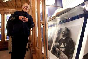 "Larry Kramer stands next to an earlier photo of himself taken by photographer Robert Giard that is part of the exhibit titled ""The Pink and the Blue: Lesbian and Gay Life at Yale and in Connecticut, 1642-2004"" on February 2, 2004. Kramer died Wednesday, May 27, 2020 in Manhattan of pneumonia. He was 84."