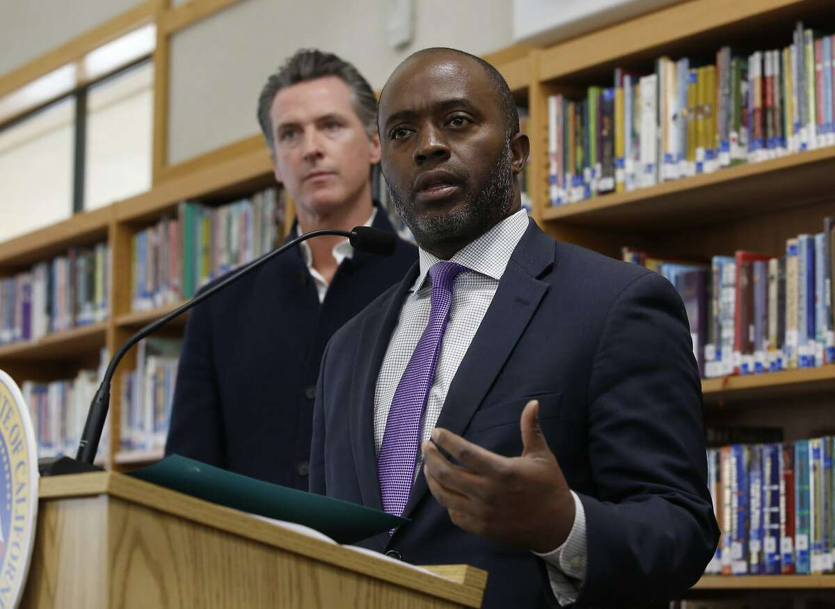 FILE - In this Oct. 31, 2019, file photo, state Superintendent of Public Instruction Tony Thurmond answers a reporter's question during a visit with Gov, Gavin Newsom, background, to Blue Oak Elementary School, in Cameron Park, Calif. Thurmond said on Wednesday, April 29, 2020, that California schools won't reopen until it can be done safely. (AP Photo/Rich Pedroncelli, File)