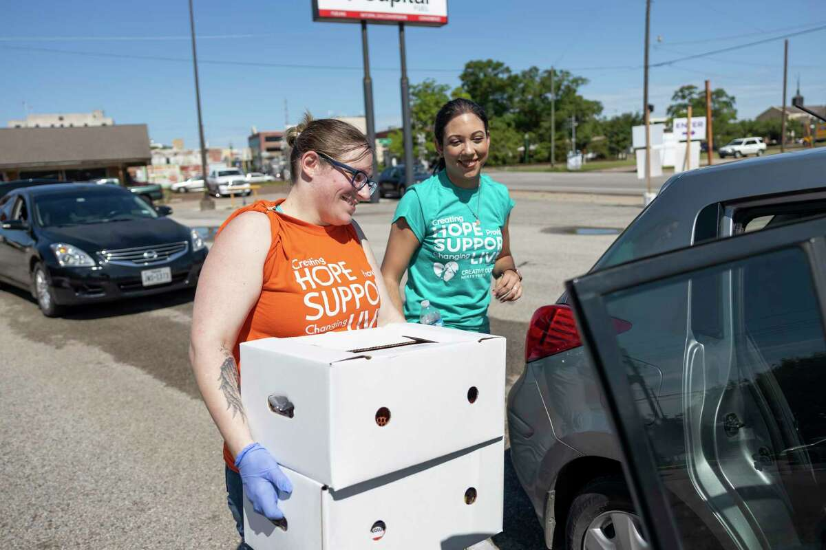Volunteers and employees of Creative Outreach Ministries load food onto vehicles during a distribution event in Conroe, Tuesday, May 26, 2020. Creative Outreach Ministries began a food distribution program last week and hope for it to span over 6-weeks offering food security for families effected by the COVID-19 pandemic.