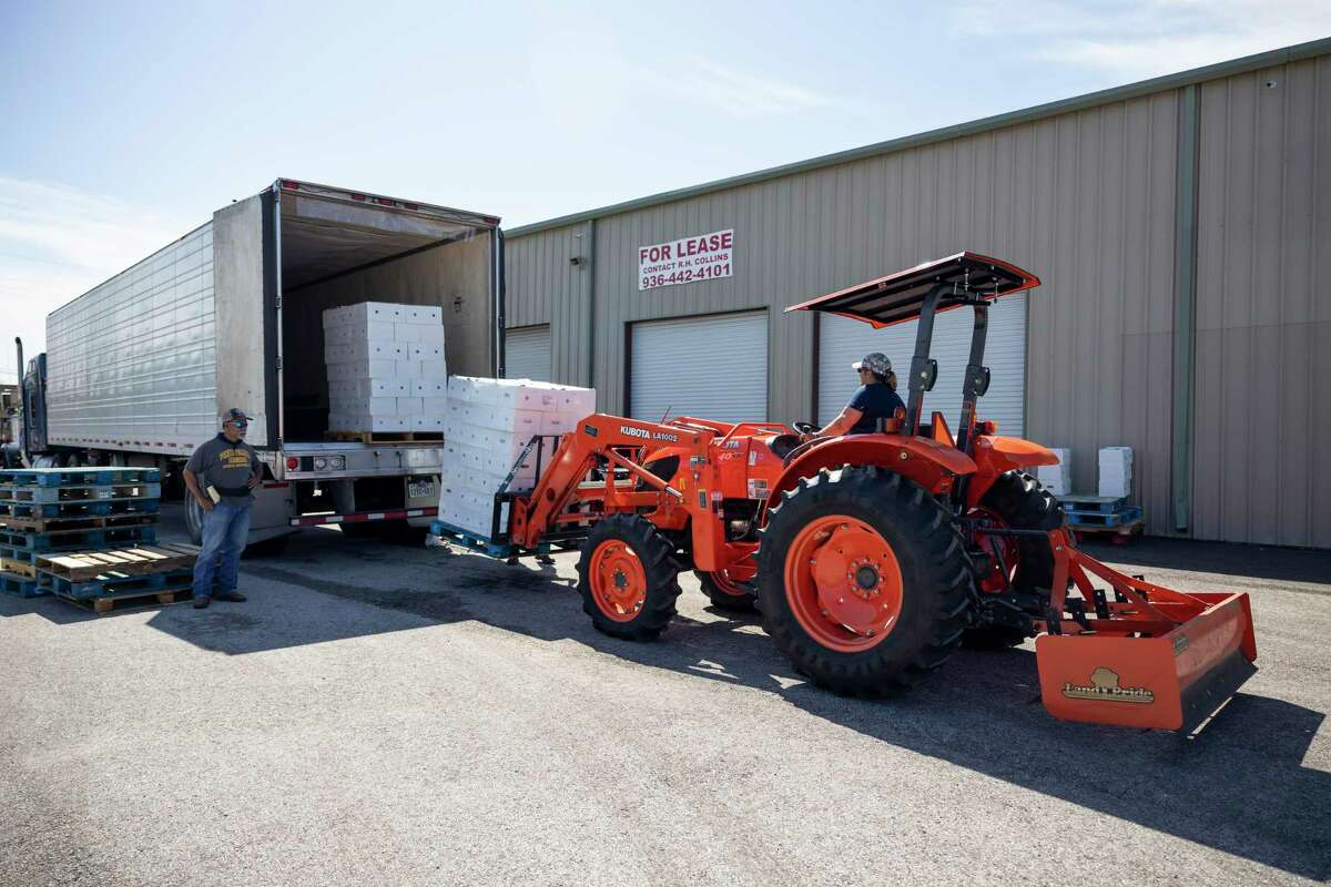 A woman steers a tractor to unload pallet of boxed food in Conroe, Tuesday, May 26, 2020. Creative Outreach Ministries served over 4,000 boxes of packaged food over the course of two hours and expect to offer more food over the following weeks.