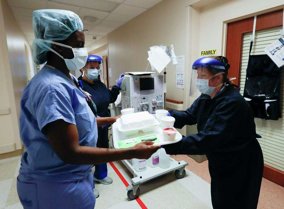 Katherine Montes a nurse with Houston Methodist's Highly Infectious Disease Unit, takes a breakfast trey for a patient while wearing personal protective equipment at Houston Methodist Continuing Care Hospital, Tuesday, May 5, 2020, in Katy. Photo: Jason Fochtman, Houston Chronicle / Staff Photographer / 2020 © Houston Chronicle