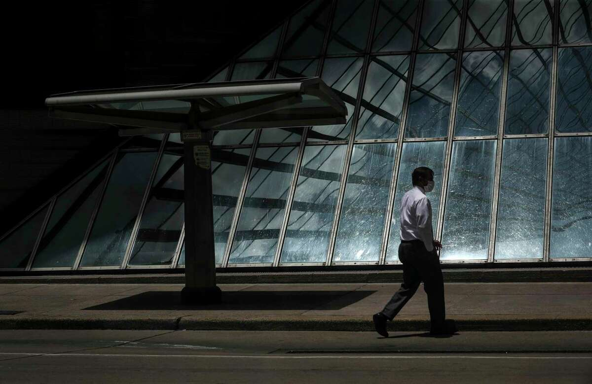 A man walks by a downtown bus stop on May 27, 2020, in Houston. Even as state officials began reopening many Texas businesses in early May, bus and rail use has continued to remain half or less of typical work days.