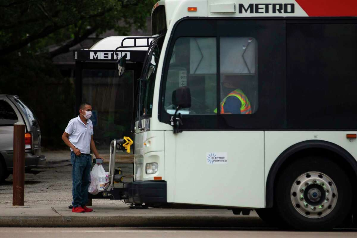A masked man prepares to board a Metropolitan Transit Authority bus on May 13, 2020, in Houston. Effective Thursday June 25, masks are required for all riders and Metro staff on buses and trains.