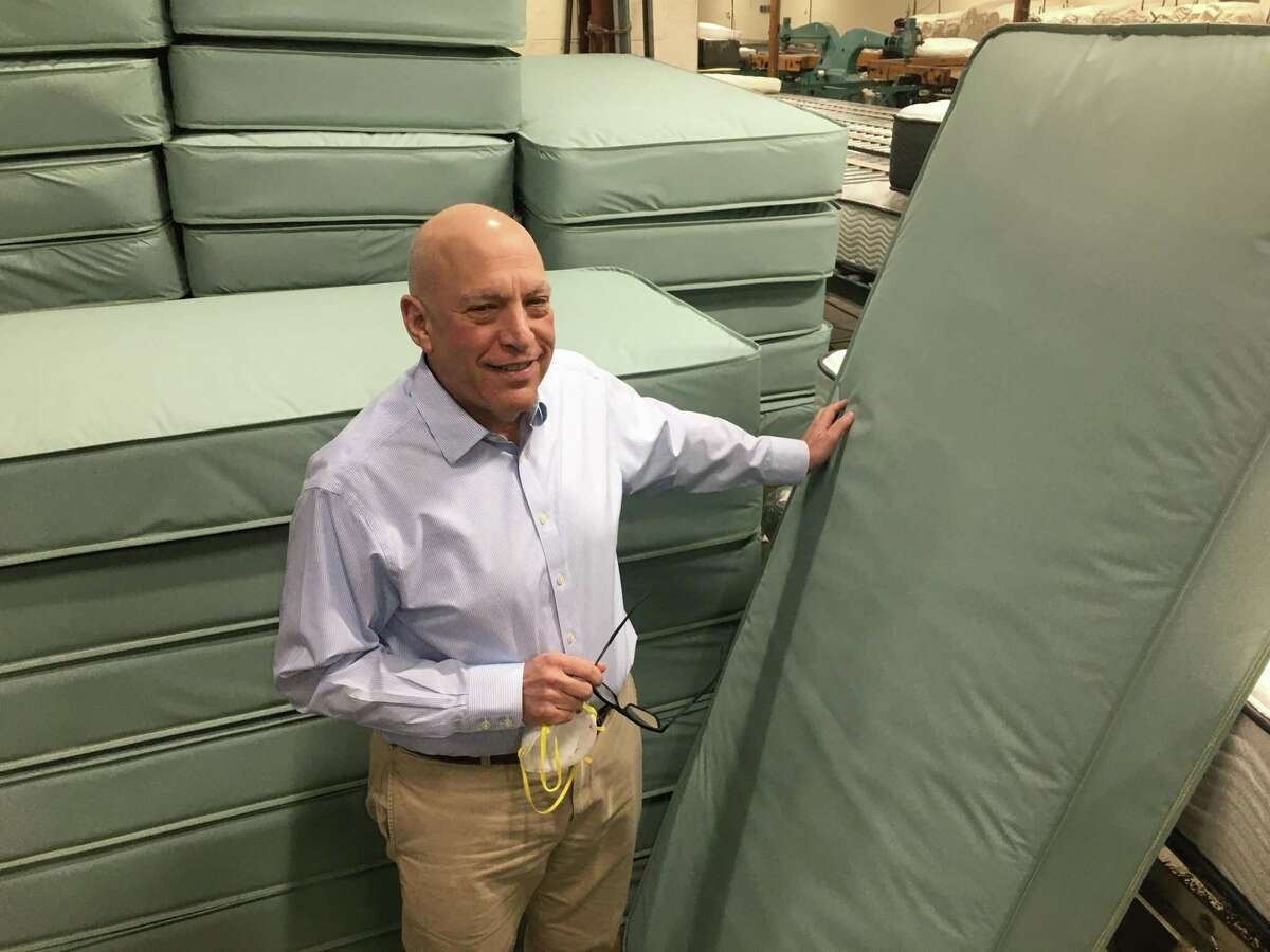 Bob Naboicheck, president of Gold Bond Mattress in Hartford, stands with mattresses made for coronavirus patient treatment at the plant, after shipping 3,500 to the state.