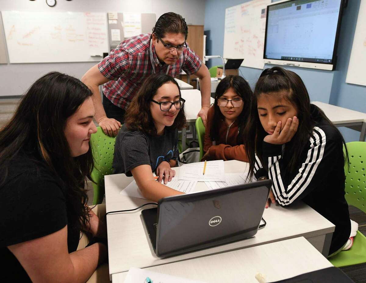 Math teacher Oscar Garcia works with students Mikaley Kester, left, Kailey Nenque-Cazares, Daisy Hernandez and Celeste Rodriguez at CAST Med High School last November. Northside ISD now is planning the network's fifth high school with an emphasis on training future teachers.
