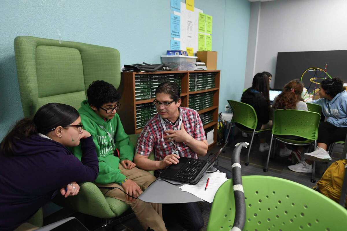 Mya Hernandez, left, and Aiden Elizondo listen as math teacher Oscar Garcia explains a solution at CAST Med High School on Friday, Nov. 22, 2019. The school offers a dual language program, as well as a curriculum that prepares students for careers in the medical field.