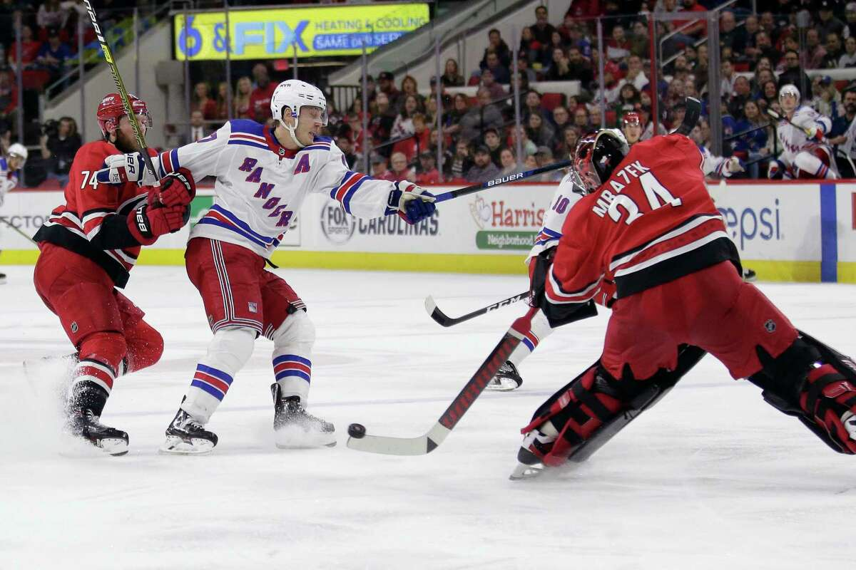 FILE - In this Nov. 7, 2019, file photo, Carolina Hurricanes goaltender Petr Mrazek (34), of the Czech Republic, blocks New York Rangers right wing Jesper Fast, of Sweden, with Hurricanes defenseman Jaccob Slavin (74) slowing Fast during the third period of an NHL hockey game in Raleigh, N.C. Carolina was one of two teams (along with Tampa Bay) that voted against the current playoff format, which doesn't reward it for being in a playoff spot when the season was paused. But the Hurricanes shouldn't need emergency goaltender David Ayres anymore with Mrazek and James Reimer healthy in net. (AP Photo/Gerry Broome, File)