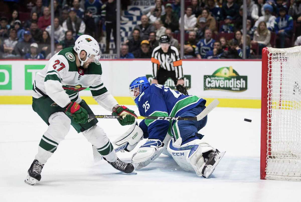 FILE - In this Feb. 19, 2020, file photo, Minnesota Wild's Alex Galchenyuk, left, scores against Vancouver Canucks goalie Jacob Markstrom, of Sweden, during the shootout in an NHL hockey game in Vancouver, British Columbia. The Canucks get Markstrom back from a knee injury, and he has had the benefit of skating at home in Sweden during the pause. (Darryl Dyck/The Canadian Press via AP, File)