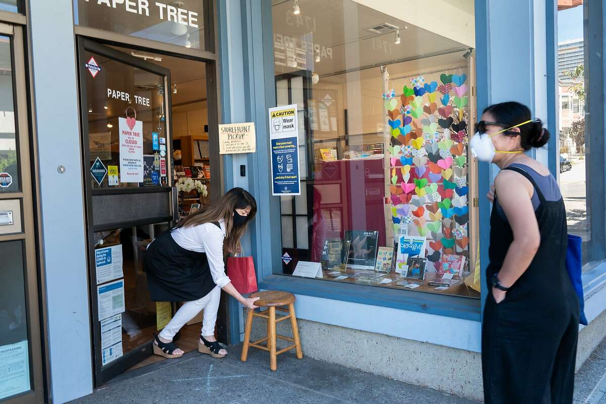 Linda Mihara, the owner of an origami shop called Paper Tree in Japantown, sets a stool to set a bag on for customer Erica Nobori on Monday, May 25, 2020, in San Francisco, Calif.
