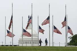 In this May 22, 2020 photo, people walk past American flags flying at half-staff at the Washington Monument in Washington. The pandemic is playing out in a divided country under a president who thrives on rousing his supporters and getting a rise out of those who don't like him, whether that means forgoing a mask, playing golf while millions hunker down or thrashing opponents on Twitter.  (AP Photo/Patrick Semansky)
