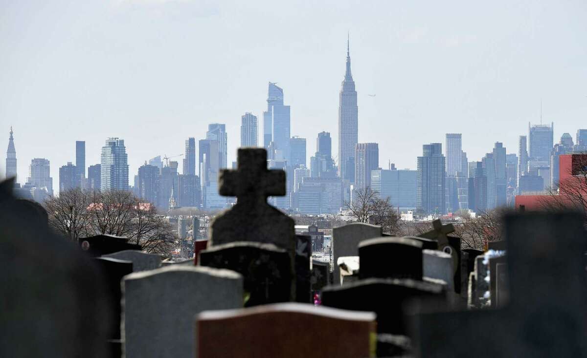 (FILES) In this file photo Gravestones from Linden Hill Methodist Cemetery are seen with the Manhattan skyline in the background in Brooklyn, New York. - The United States has now recorded more than 100,000 coronavirus-related deaths, Johns Hopkins University reported Wednesday -- a somber milestone and by far the highest total in the world. The country reported its first death about three months ago. Since then, nearly 1.7 million infections have been tallied nationwide, according to the Baltimore-based school. The actual number of deaths and infections is believed to be higher, experts say. (Photo by Angela Weiss / AFP) (Photo by ANGELA WEISS/AFP via Getty Images)