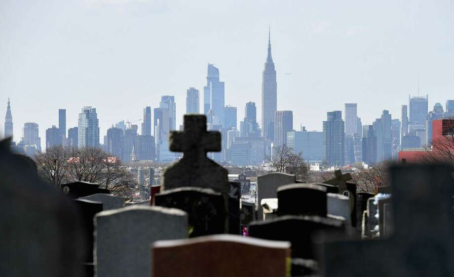 (FILES) In this file photo Gravestones from Linden Hill Methodist Cemetery are seen with the Manhattan skyline in the background in Brooklyn, New York. - The United States has now recorded more than 100,000 coronavirus-related deaths, Johns Hopkins University reported Wednesday -- a somber milestone and by far the highest total in the world. The country reported its first death about three months ago. Since then, nearly 1.7 million infections have been tallied nationwide, according to the Baltimore-based school. The actual number of deaths and infections is believed to be higher, experts say. (Photo by Angela Weiss / AFP) (Photo by ANGELA WEISS/AFP via Getty Images) Photo: ANGELA WEISS / AFP or licensors