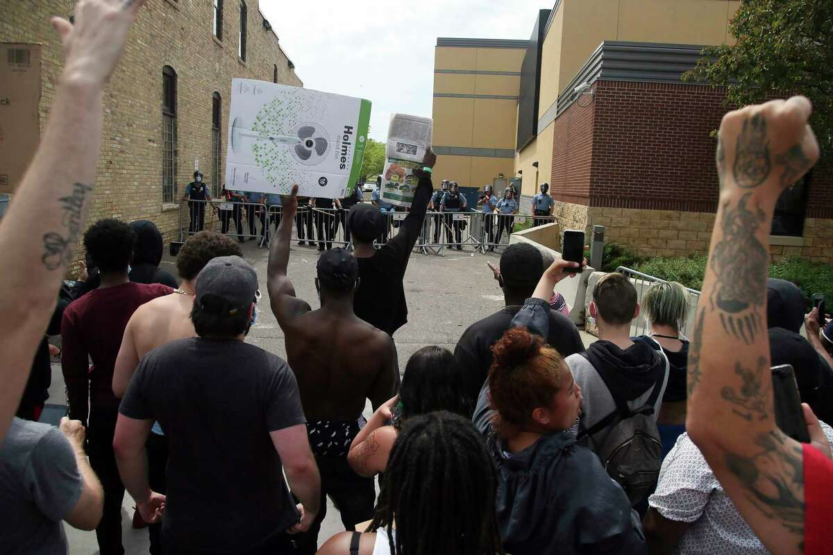 Minneapolis police stand guard against protesters at the Third Precinct, Wednesday, May 27, 2020, as people protest the arrest and death of George Floyd who died in police custody Monday night in Minneapolis after video shared online by a bystander showed a white officer kneeling on his neck during his arrest as he pleaded that he couldn't breathe. (AP Photo/Jim Mone)