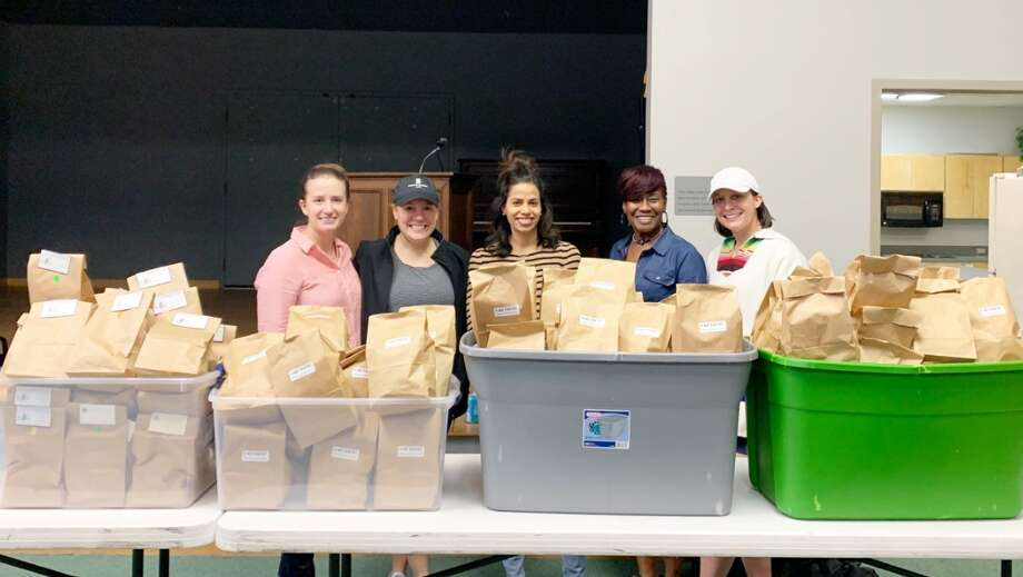 Junior League of Midland members Katie McBryde, from left, Anne Reese, Evelyn Serrano, Gwendolyn Taylor and Diana Martin pose with bags filled with hygiene products, part of the nonprofit's Pink Pantry program. Photo: Courtesy Photo