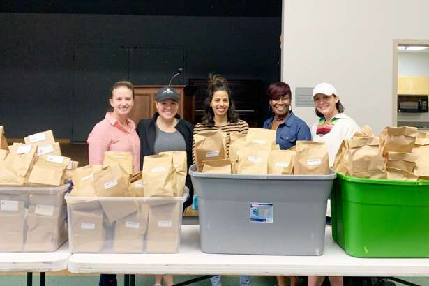 Junior League of Midland members Katie McBryde, from left, Anne Reese, Evelyn Serrano, Gwendolyn Taylor and Diana Martin pose with bags filled with hygiene products, part of the nonprofit's Pink Pantry program.
