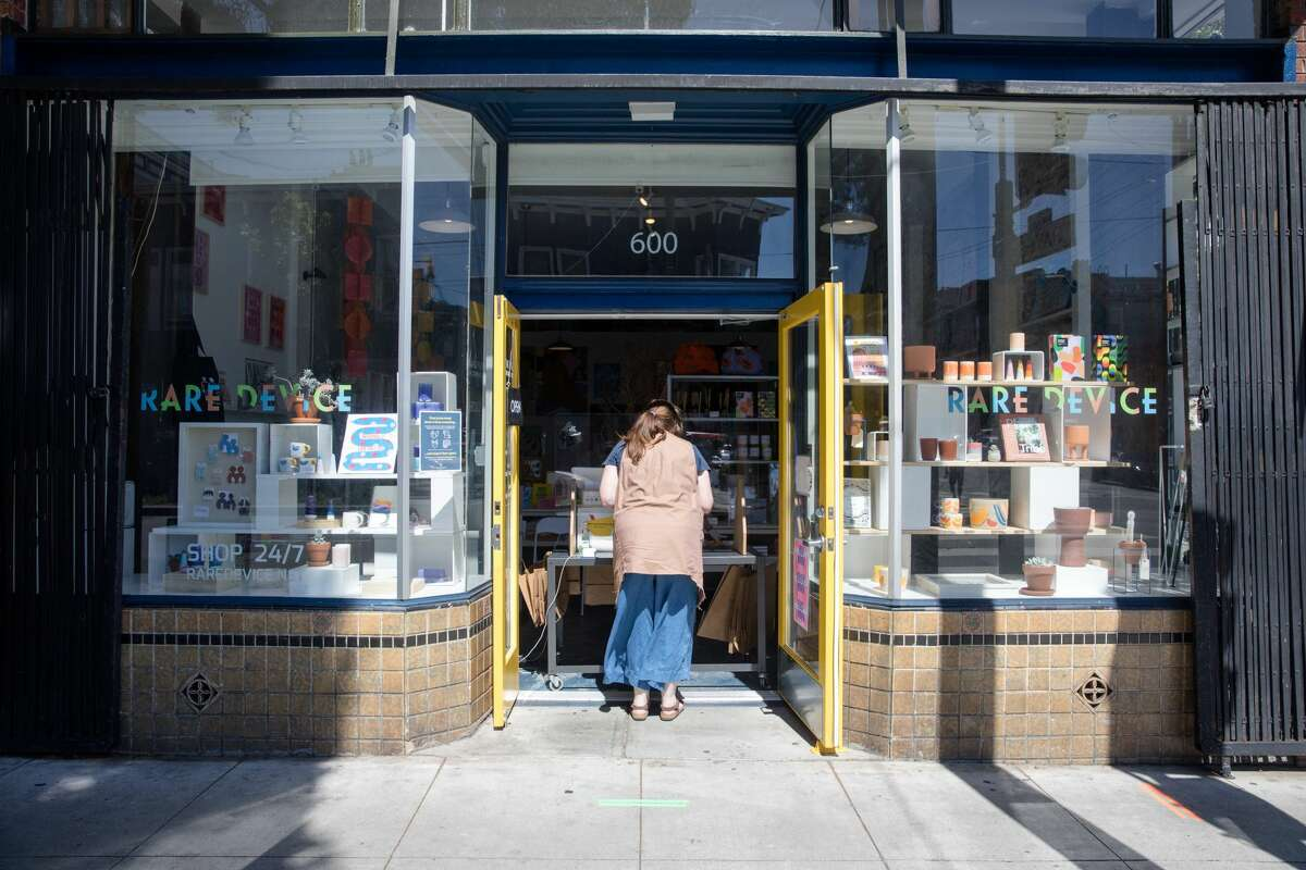Darcie Bell waits at the front door to pick up her online order at Rare Device on Divisadero Street in San Francisco on May 27, 2020.