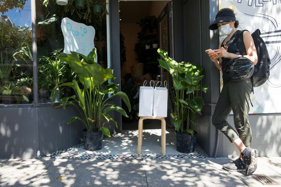 Having arrived to pick up her order, Shelley Davies uses her cell phone to buy an additional item online from Plants and Friends on Fillmore Street in San Francisco on May 27, 2020. It is one of many retail stores that have recently opened curbside or door service in San Francisco. Photo: Shelley Davies Waits For Her Delivery At Plants And Friends., Douglas Zimmerman/SFGate / SFGate