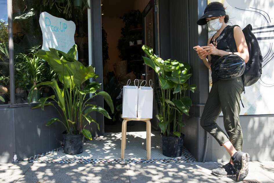 Having arrived to pick up her order, Shelley Davies uses her cell phone to buy an additional item online from Plants and Friends on Fillmore Street in San Francisco on May 27, 2020. It is one of many retail stores that have recently opened curbside or door service in San Francisco.