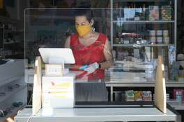 Giselle Gyalzeen of Rare Device rings up an order on her doorfront register on May 27, 2020. It is one of many retail stores that have recently opened curbside or door service in San Francisco.