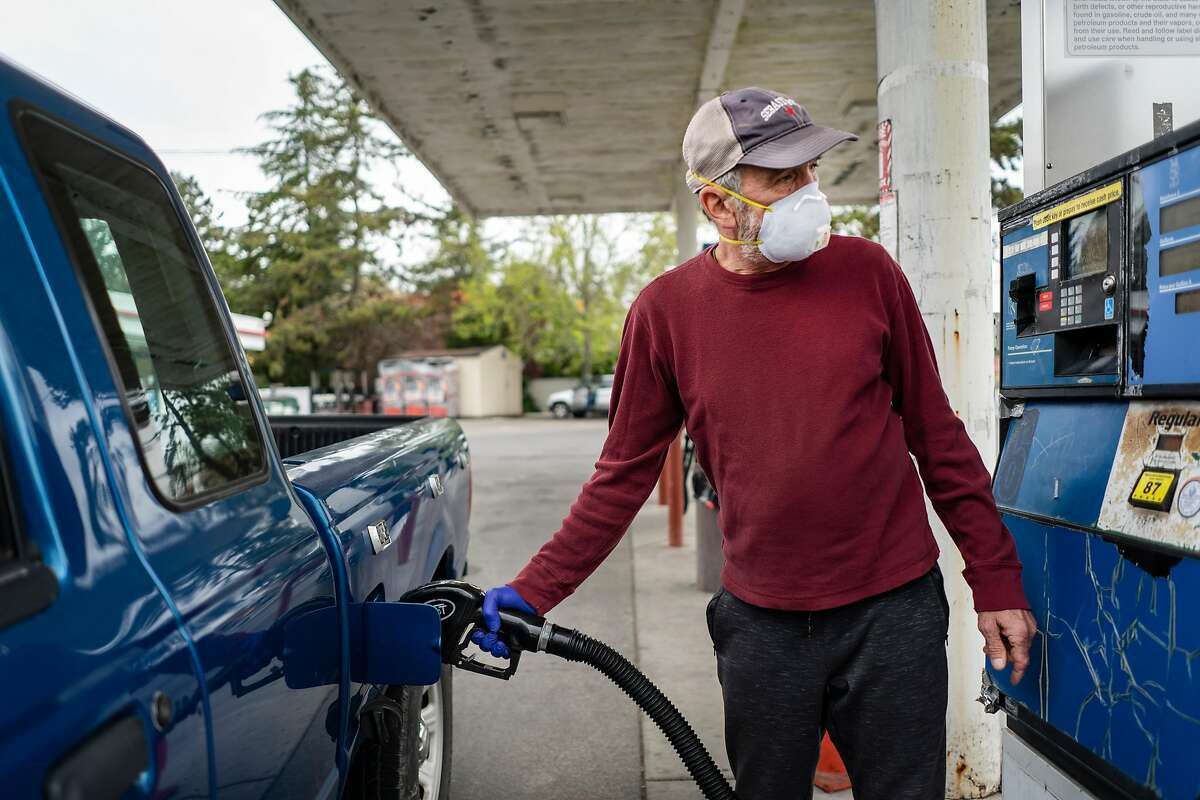 Paul Berg, 64, gets gas wearing a mask and gloves at a gas station in Sebastopol, California on April 17, 2020.