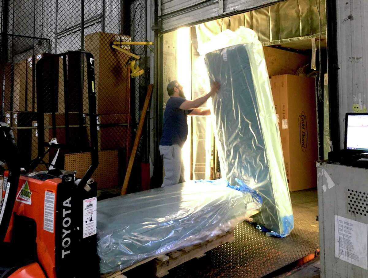 Gold Bond Mattress, a Hartford company since 1899, supplied 3,500 mattresses to the state of Connecticut for emergency hospital overflow in the coronavirus crisis. Pictured are employees Angela Cruz, of Hartford, a 20-year employee, working on a stitching machine and talking with Juan DeJesus of East Hartford, an 18-year veteran; and Sonny Rodriguez, a 22-year employee, at the loading dock.