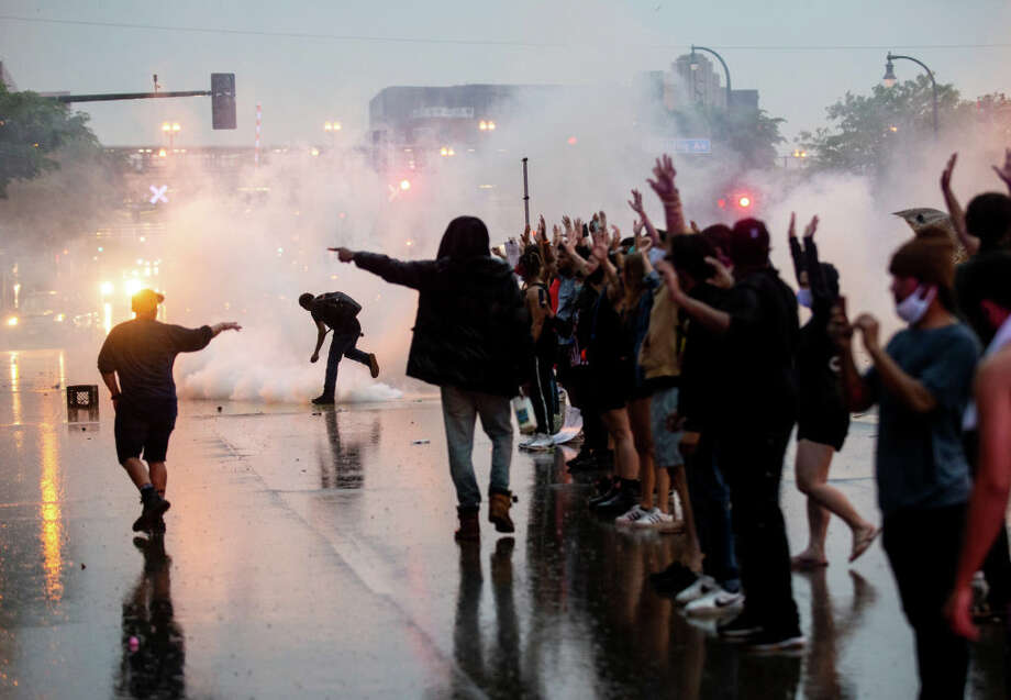 """MINNEAPOLIS, MN - MAY 26: Tear gas is fired as protesters clash with police while demonstrating against the death of George Floyd outside the 3rd Precinct Police Precinct on May 26, 2020 in Minneapolis, Minnesota. Four Minneapolis police officers have been fired after a video taken by a bystander was posted on social media showing Floyd's neck being pinned to the ground by an officer as he repeatedly said, """"I can't breathe"""". Floyd was later pronounced dead while in police custody after being transported to Hennepin County Medical Center. (Photo by Stephen Maturen/Getty Images) Photo: Stephen Maturen/Getty Images / 2020 Getty Images"""