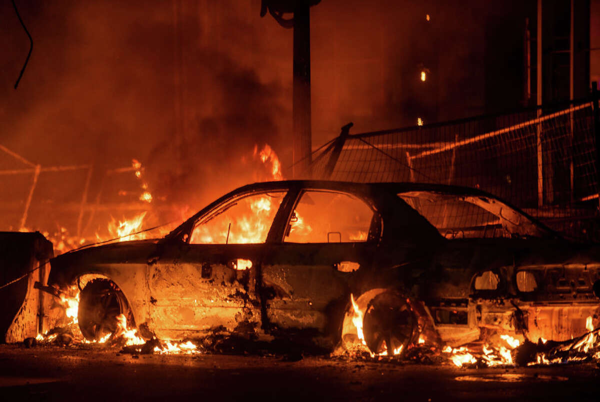MINNEAPOLIS, MN - MAY 27: A car burns near the Third Police Precinct on May 27, 2020 in Minneapolis, Minnesota. A number of businesses and homes were damaged as the area has become the site of an ongoing protest after the police killing of George Floyd. Four Minneapolis police officers have been fired after a video taken by a bystander was posted on social media showing Floyd's neck being pinned to the ground by an officer as he repeatedly said,