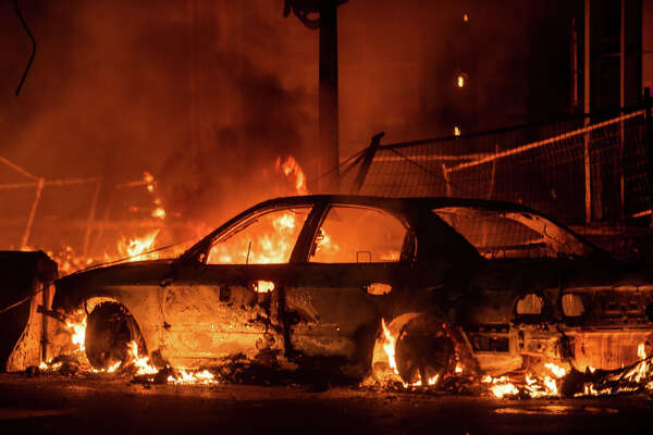 "MINNEAPOLIS, MN - MAY 27: A car burns near the Third Police Precinct on May 27, 2020 in Minneapolis, Minnesota. A number of businesses and homes were damaged as the area has become the site of an ongoing protest after the police killing of George Floyd. Four Minneapolis police officers have been fired after a video taken by a bystander was posted on social media showing Floyd's neck being pinned to the ground by an officer as he repeatedly said, ""I can't breathe"". Floyd was later pronounced dead while in police custody after being transported to Hennepin County Medical Center. (Photo by Stephen Maturen/Getty Images)"