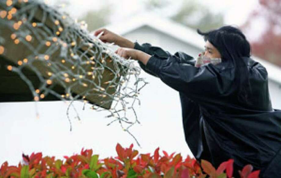 Cold weather doesn't stop Harmony Brundrett from trying to finish decorating her home on East Tanglewood Drive in New Braunfels with holiday lights. She just put on a warm coat and covered her nose and mouth.