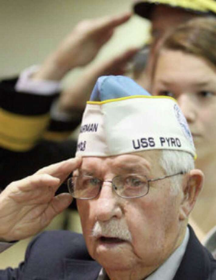 Don Green of Allyn, Wash., a Pearl Harbor survivor, salutes the colors during a Veterans Day ceremony  in Bremerton, Wash. Green was on the USS Pyro, an ammunition ship.