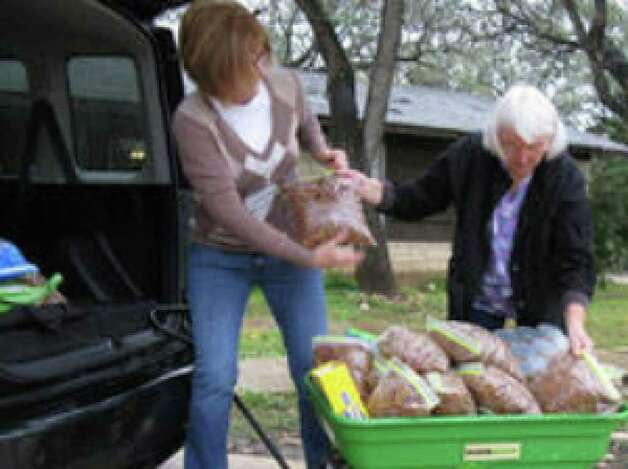 Helotes Humane Society volunteers Stephanie Dunlea (left) and Lois Tanigawa pack up pet food at the organization's pet food bank on Bandera Road for distribution to needy pet owners. The organization wants to open a shelter capable of holding at least 25 dogs and 25 cats.