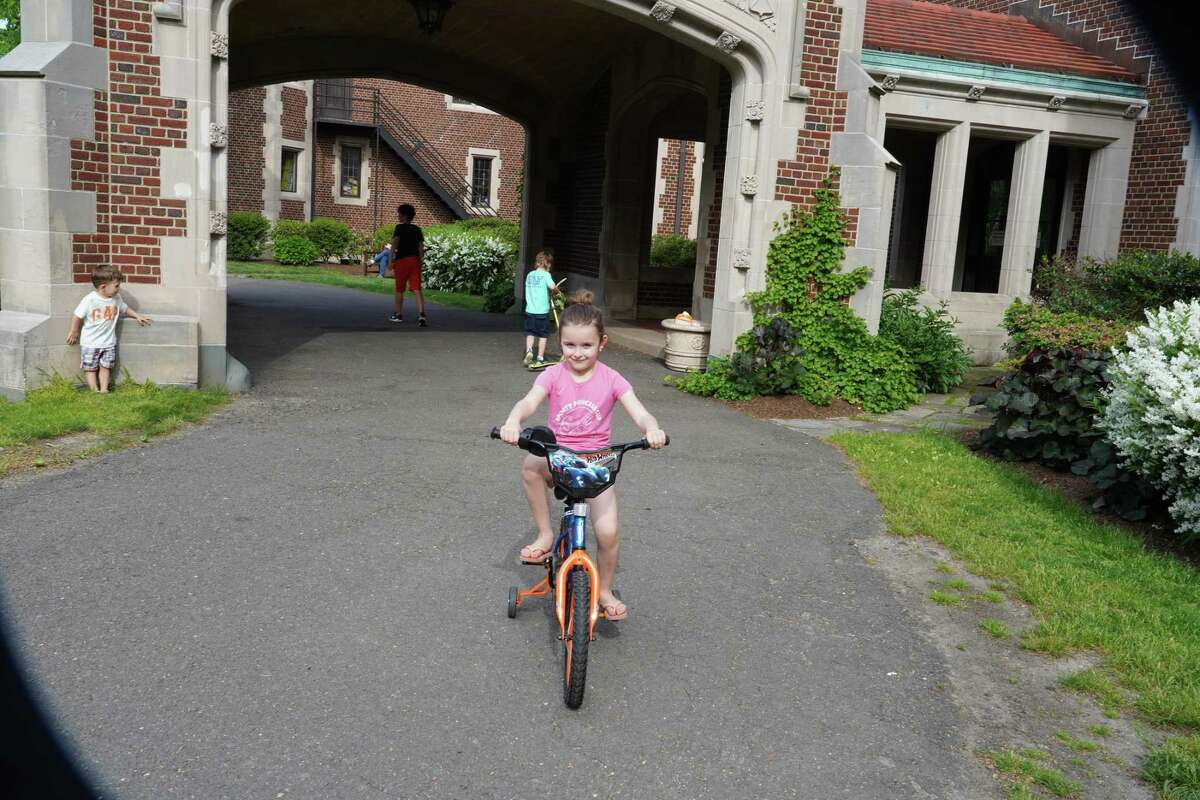 Nadiya Pivtorak, six years old, was riding her friend's bike in front of the Waveny House in New Canaan on Wednesday, May 27, 2020. Business is not as good as it might be for bicycle stores, because there are problems with bicycle distribution, since most bikes come from Asia.