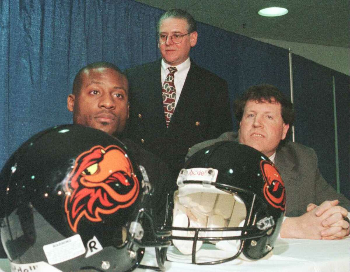Times Union photo by JAMES GOOLSBY-MAR. 18,1997-(L. TO R.)-EDDIE BROWN , ALBANY FIREBIRDS RECEIVER. GLENN MAZULA, OWNER OF THE FIREBIRDS AND MIKE DAILEY, FIREBIRDS HEAD COACH. DISPLAY THE NEW TEAM LOGO ON THE HELMETS AND THE NEW TEAM SONG AT PRESS CONFERENCE
