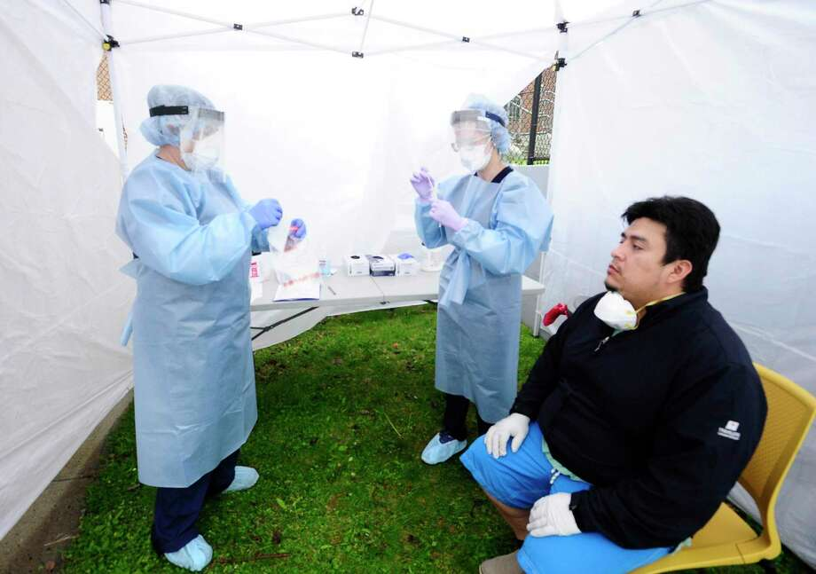 Nurse Practitioners Heather Dawson and Julianna Barresi test Greenwich resident Walter Aucay, 36, with an oral coronavirus swab at a testing site set up at the Family Center at Wilbur Peck. Photo: Matthew Brown / Hearst Connecticut Media / Stamford Advocate