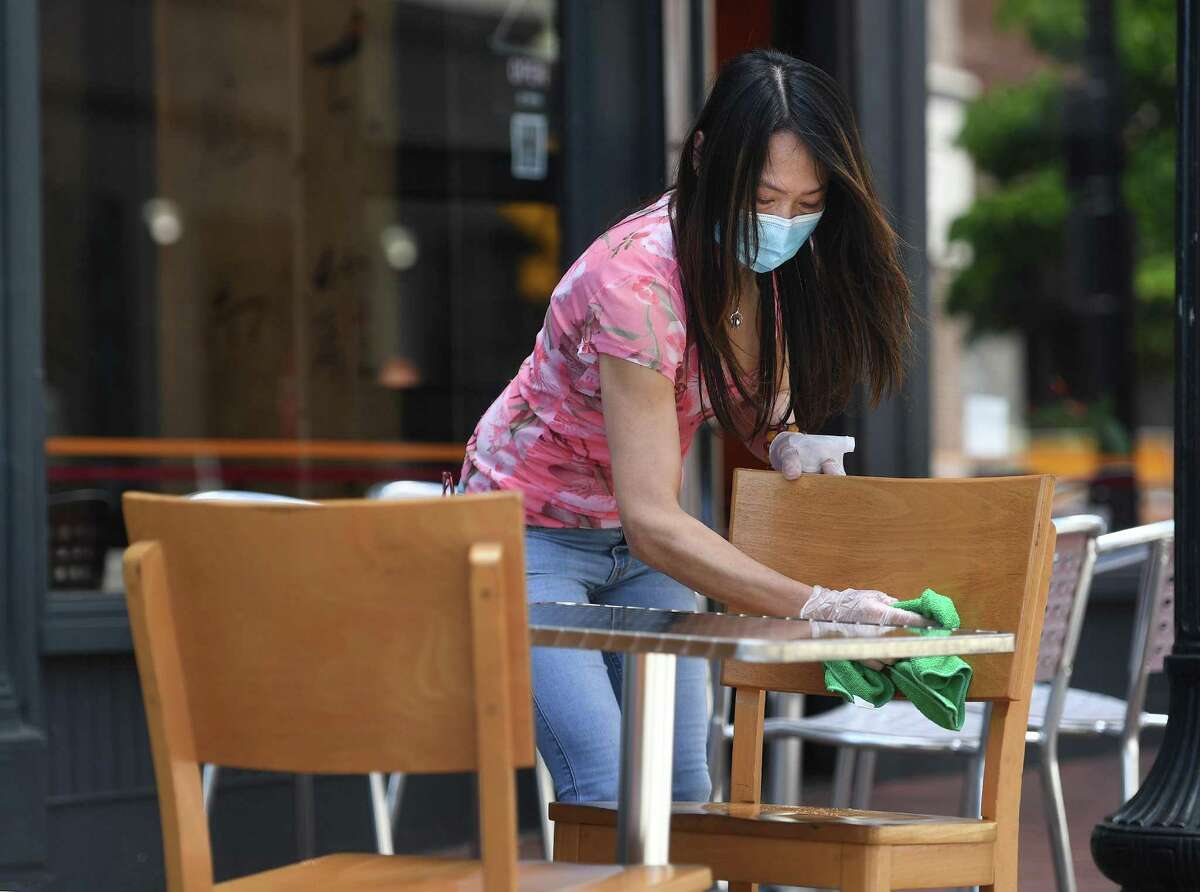 A waitress cleans a table on Wednesday, May 27, 2020, on the restaurant row of Washington Street in Norwalk, Conn.