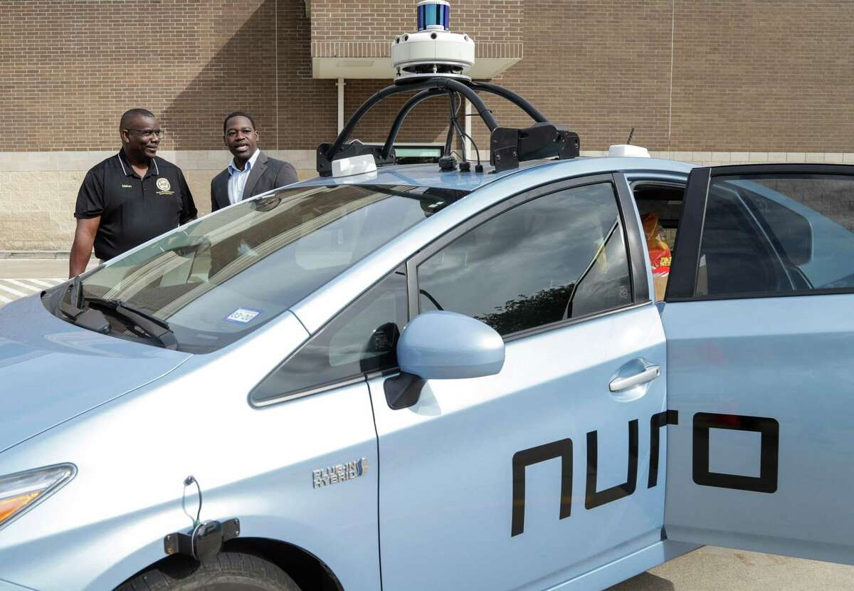 Sola Lawal, right, product operations manager at Nuro, explains autonomous driving technology to Melvin Hopkins, who works for Houston City Council Member Martha Castex-Tatum, before a press conference to announce a delivery service from Kroger using autonomous-driving technology, at the Kroger store on South Post Oak Boulevard Tuesday, April 16, 2019, in Houston.