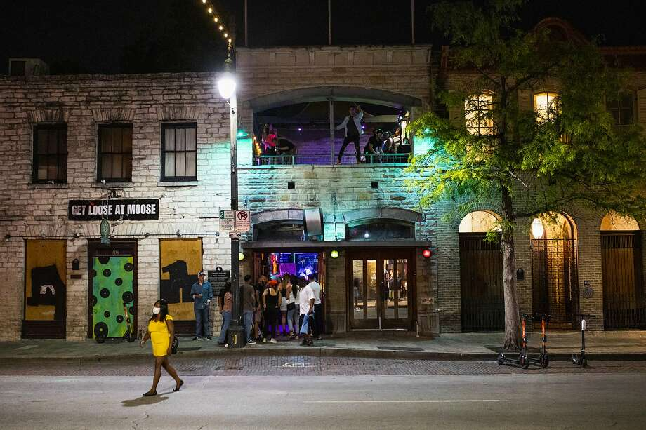 People stand in line to enter a bar on Sixth Street at night in downtown Austin, Texas, U.S., on Saturday, May 23, 2020. Texas bars, bowling alleys and other businesses were able to reopen for the start of Memorial Day weekend as part of Governor Greg Abbott's efforts to revive the state's shattered economy. Photographer: Alex Scott/Bloomberg Photo: Alex Scott, Bloomberg