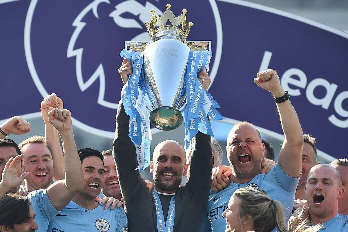 (FILES) In this file photo taken on May 12, 2019 Manchester City's Spanish manager Pep Guardiola holds up the Premier League trophy as he's surrounded by his staff after their 4-1 victory in the English Premier League football match between Brighton and Hove Albion and Manchester City at the American Express Community Stadium in Brighton, southern England. - The Premier League season is set to restart on June 17, three months after it was suspended due to the coronavirus pandemic, British media reported on Thursday, May 28. (Photo by Glyn KIRK / AFP) / RESTRICTED TO EDITORIAL USE. No use with unauthorized audio, video, data, fixture lists, club/league logos or 'live' services. Online in-match use limited to 75 images, no video emulation. No use in betting, games or single club/league/player publications. / (Photo by GLYN KIRK/AFP via Getty Images)