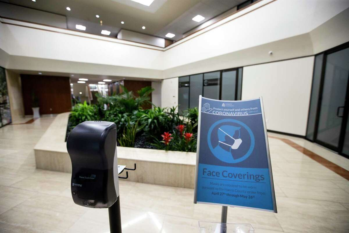 A sign requiring face coverings stands next to a hand sanitizer dispenser is in the lobby of the building where Foster Marketing has its office on Wednesday, May 27, 2020 in Houston. Foster Marketing is one of the offices that felt comfortable returning to the office, in part because the office is so spacious and they have their own offices.