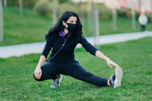 Young woman stretching on grass in public park