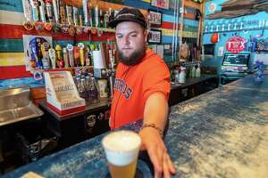 Neches Brewing Company bartender Alex Bass gives a beer to a waiting customer. Friday saw the reopening of bars in Texas with limited capacity and more cleaning and sterilizing than before the Covid pandemic. Photo made on May 22, 2020.  Fran Ruchalski/The Enterprise