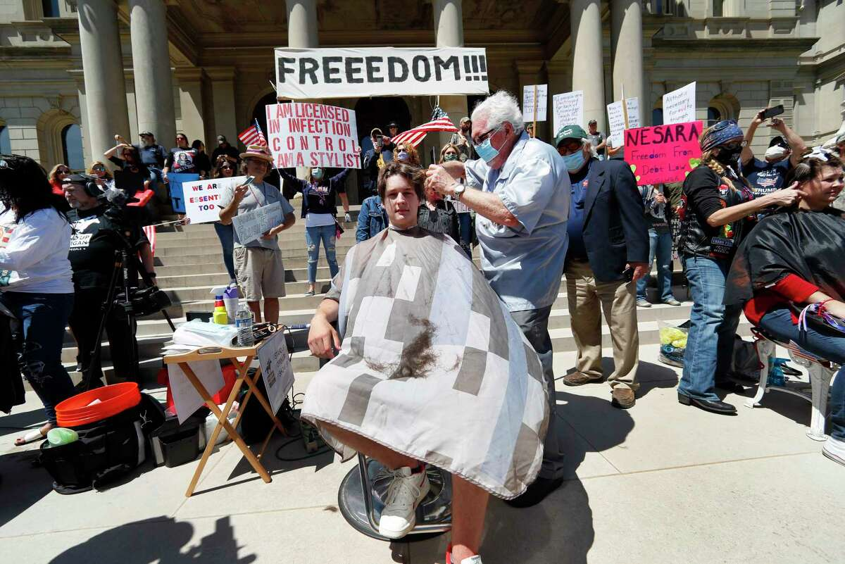 Barber Karl Manke, of Owosso, gives a free haircut to Parker Shonts on the steps of the State Capitol during a rally May 20 in Lansing. (AP Photo/Paul Sancya)