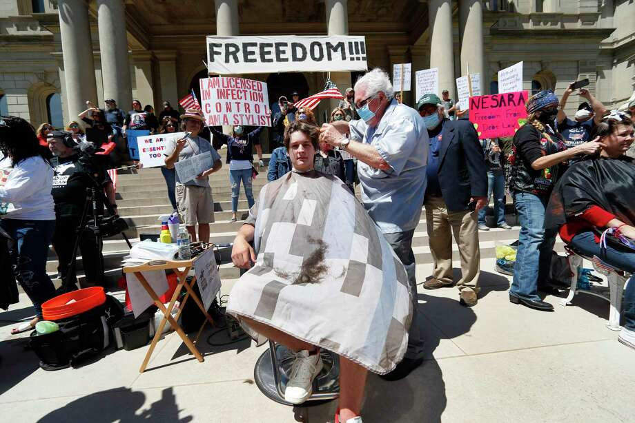 Barber Karl Manke, of Owosso, gives a free haircut to Parker Shonts on the steps of the State Capitol during a rally May 20 in Lansing. (AP Photo/Paul Sancya) / Copyright 2020 The Associated Press. All rights reserved