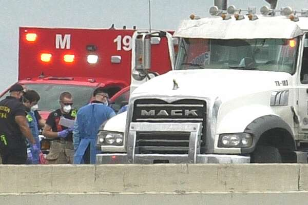 Houston police officers and Houston Fire Department paramedics work the scene of an 18-wheeler crash along the Eastex Freeway ramp to the East Loop on Thursday, May 28, 2020.