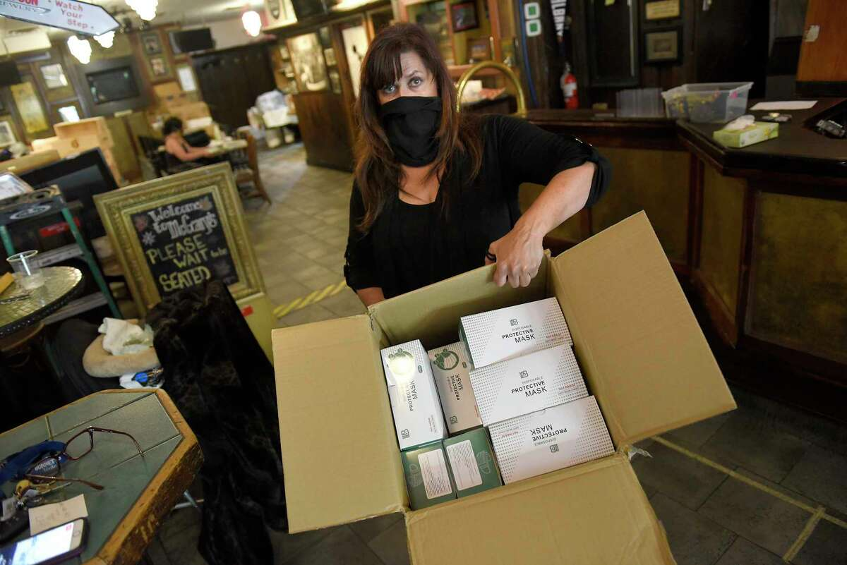 Tess Collins, owner of McGeary?•s Pub, holds a box of face masks she gives out to customers who don't have one on Thursday, May 28, 2020 in Albany, N.Y. (Lori Van Buren/Times Union)