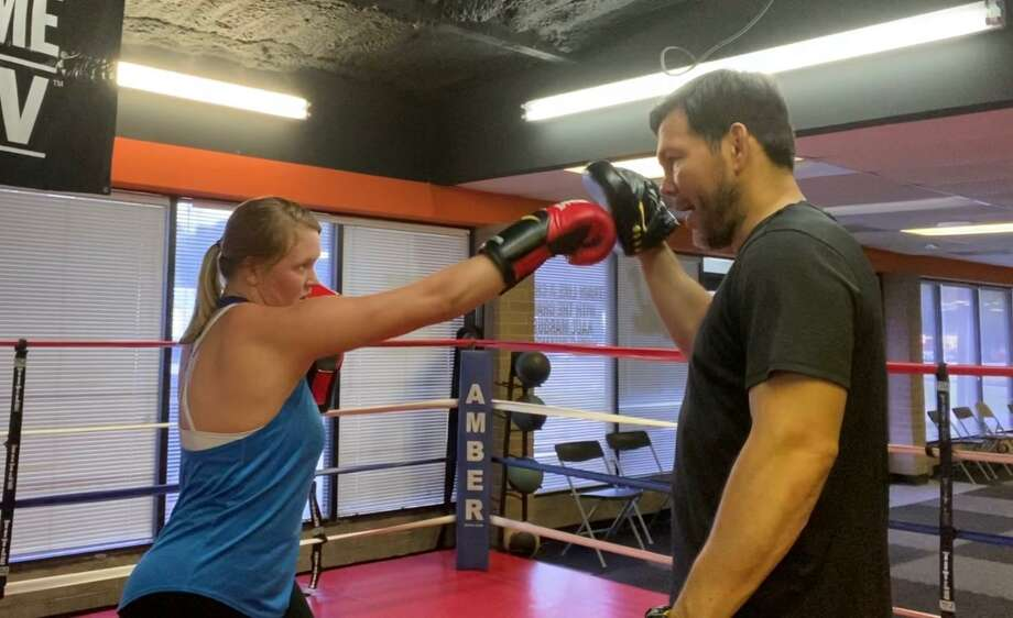 Kendall Searcy takes a private lesson from World Champion Raul Marquez at his boxing and fitness gym in Humble. The gym has reopened with adjusted hours and new cleaning protocols. Photo: Submitted