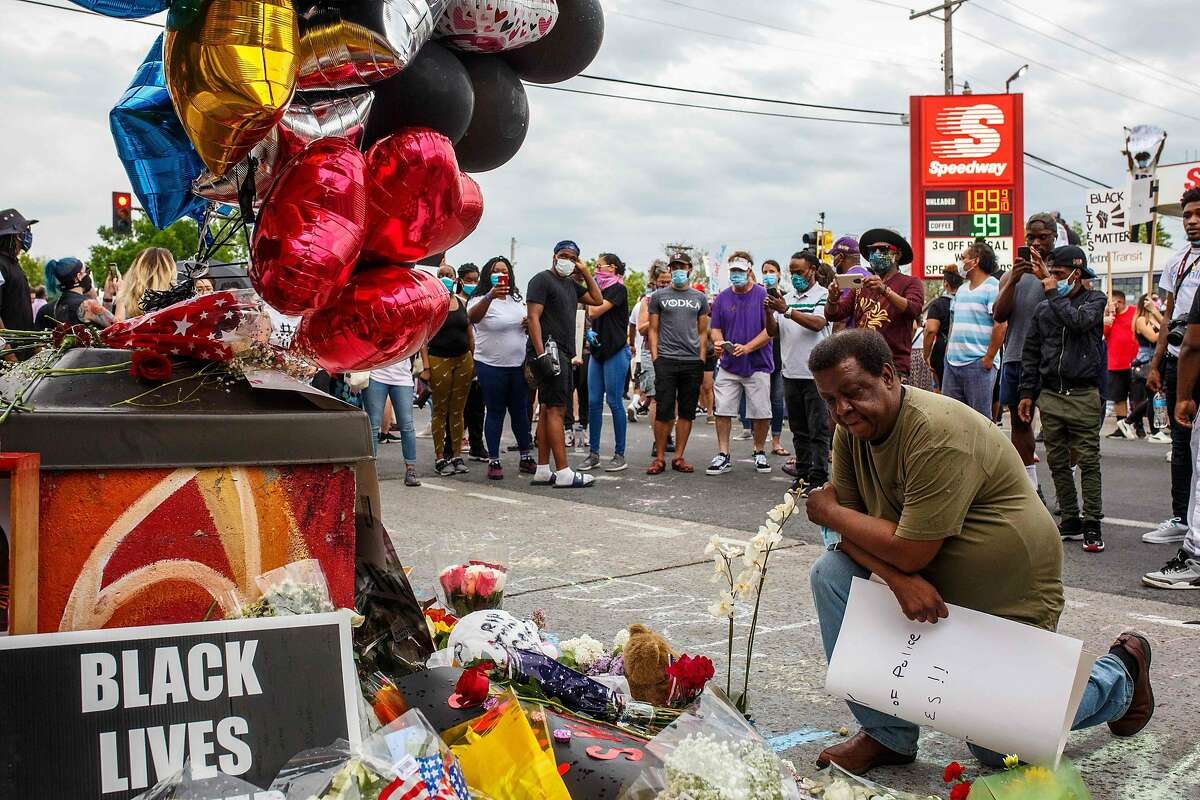 A man prays in front of a makeshift memorial in honor of George Floyd who died in custody on May 26, 2020 in Minneapolis, Minnesota. - A video of a handcuffed black man dying while a Minneapolis officer knelt on his neck for more than five minutes sparked a fresh furor in the US over police treatment of African Americans Tuesday. Minneapolis Mayor Jacob Frey fired four police officers following the death in custody of George Floyd on Monday as the suspect was pressed shirtless onto a Minneapolis street, one officer's knee on his neck. (Photo by Kerem Yucel / AFP) (Photo by KEREM YUCEL/AFP via Getty Images)
