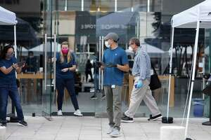 Apple employees wait for screened customers at the front door at Highland Village Apple Store, in Houston, on Wednesday, May 27, 2020. Consulting and research firm Gartner predicts that global shipments of mobile phones will drop about 15 percent in 2020 because of disruption from the pandemic.