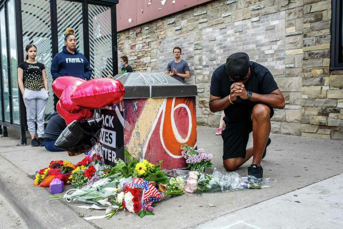 A man prays in front of a memorial of George Floyd who died in custody this month in Minneapolis, Minn. On video Floyd repeatedly tells the officer with a knee on his neck that he can't breathe, but to no avail.